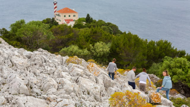 WS of group of friends climbing rocky hill on island with lighthouse