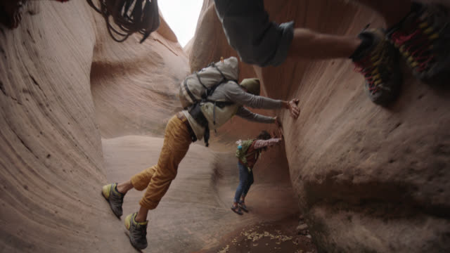 Group of friends climbing through narrow slot canyon maintain balance on rock walls over water.