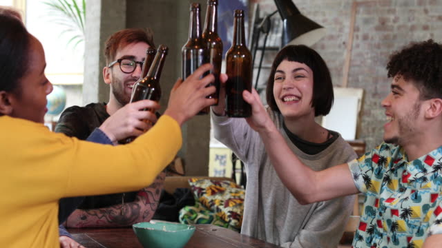 Group of friends clinking beer bottles at a house party