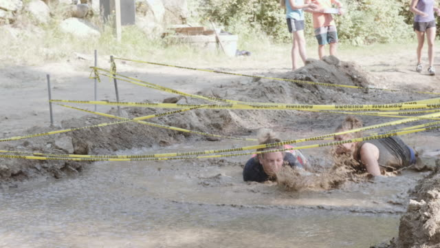 uhd 4k: group of friends competing in a fun mud run race together - superwoman stock videos and b-roll footage