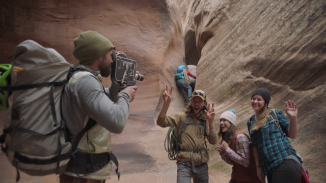 Group of friends dance and strike funny poses for man with film camera in sandstone slot canyon.