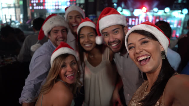group of friends dancing at a bar wearing santa's hat smiling to camera as they take a selfie - colombia stock videos and b-roll footage