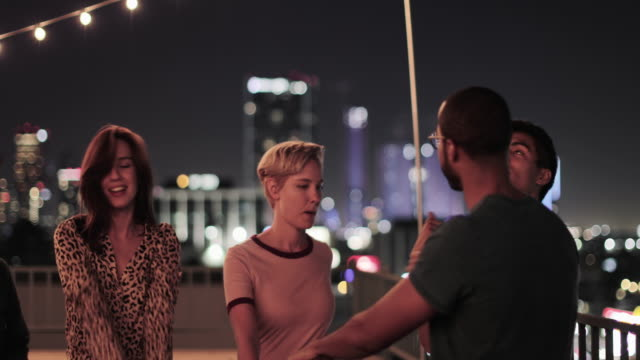 group of friends dancing at a rooftop party - five people stock-videos und b-roll-filmmaterial