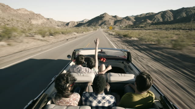 Group of friends drive down lonely desert road talking and laughing, girl holds hand in the wind
