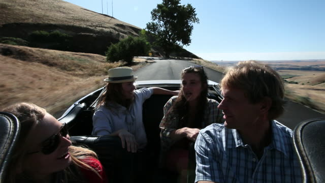 ms group of friends driving convertible on desert road two women in backseat jumping up hat blowing away in wind/washington, usa - オープンカー点の映像素材/bロール