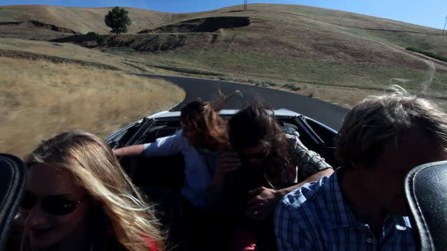 MS Group of friends driving convertible on desert road windmills in background/Washington, USA