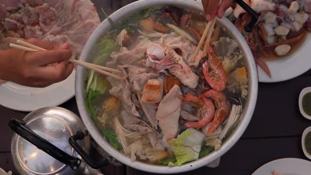 stockvideo's en b-roll-footage met groep vrienden eet thaise bbq moo kra ta - japanse gerechten
