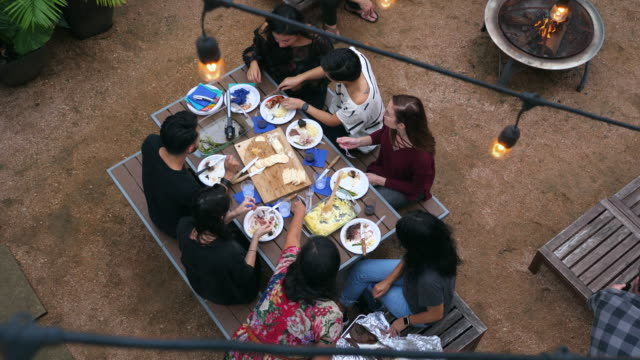 HA MS Group of friends eating food at table during barbecue on summer evening