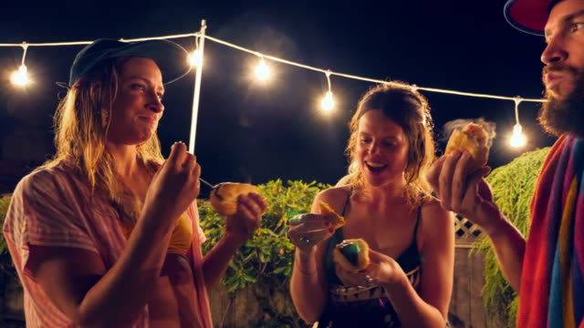 PAN Group of friends eating hot dogs in backyard after pool party on summer evening