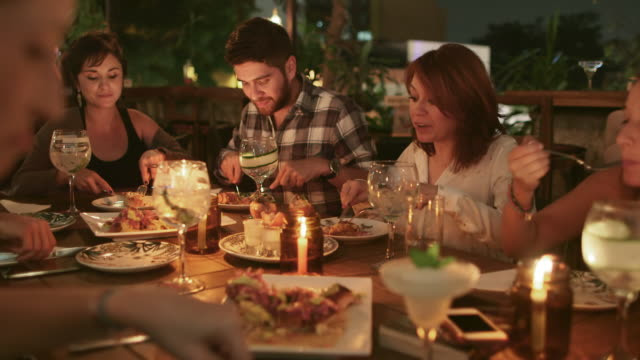 vidéos et rushes de group of friends eating in a restaurant / medellin, colombia - candlelight