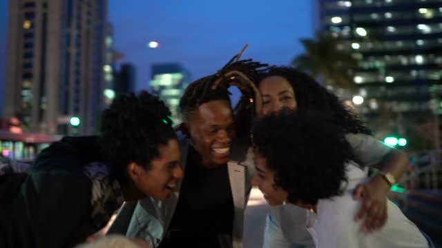 vídeos de stock e filmes b-roll de group of friends embracing and applauding outdoors - pardo brasileiro