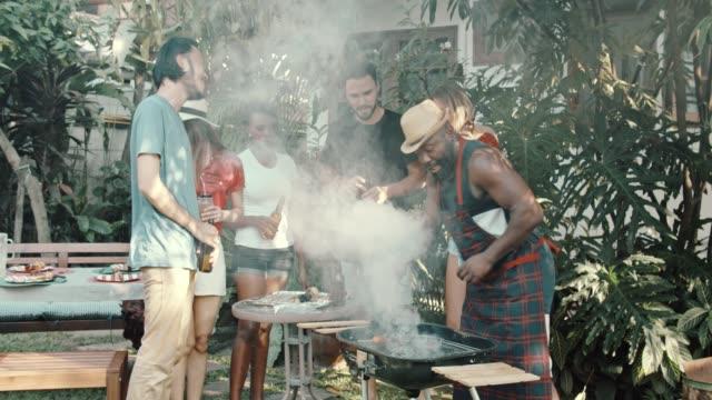 vidéos et rushes de groupe d'amis appréciant une partie de barbecue - barbecue