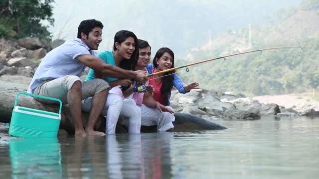 vídeos de stock e filmes b-roll de group of friends enjoying at riverbank  - geleira portátil