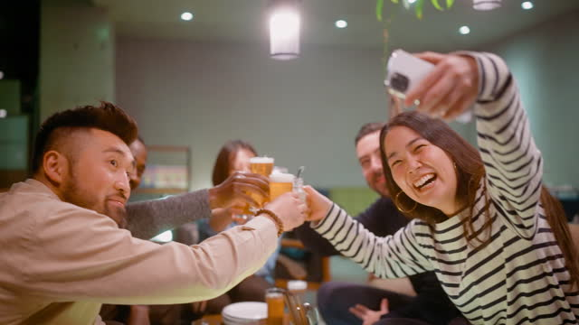 group of friends enjoying beer and cocktails and taking selfie with smart phone - mid adult men stock videos & royalty-free footage