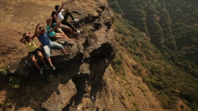 group of friends enjoying on a cliff of mountain - braccio umano video stock e b–roll