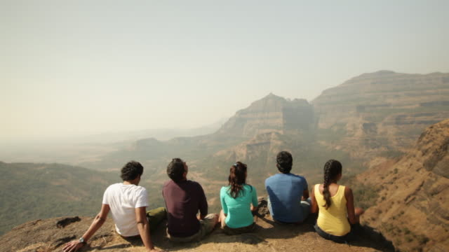 Group of friends enjoying on a cliff of mountain