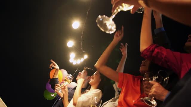 Gruppe von Freunden genießen Partei und werfen Konfetti. Freunde, die Spaß an Party auf dem Dach. Gruppe von Freunden auf dem Dach, Spaß zu haben. Silvester party