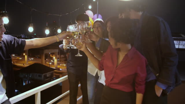 group of friends enjoying party and throwing confetti. friends having fun at rooftop party.group of friends at rooftop having fun. new year's party - twilight stock videos & royalty-free footage