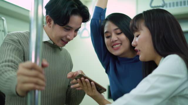 メトロ列車で携帯電話でビデオを見て楽しむ友人のグループ - 内部点の映像素材/bロール