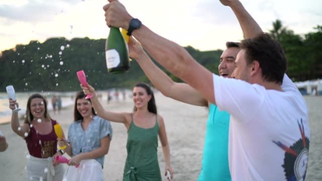 group of friends / family celebrating new year at beach - champagne stock videos & royalty-free footage