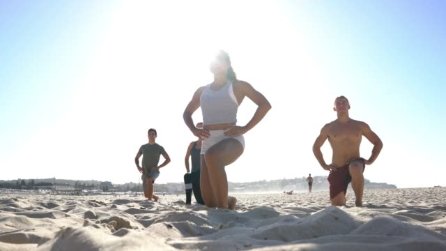 group of friends following coach doing a drill of exercises at the beach - fitness instructor stock videos & royalty-free footage