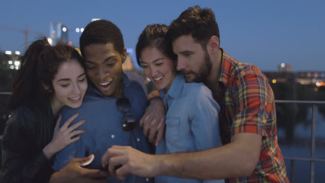 group of friends gather around smartphone on pedestrian bridge - 動画関連点の映像素材/bロール