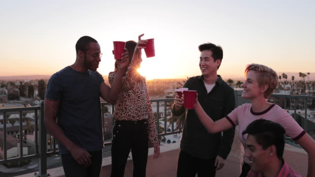 group of friends gathering on a rooftop for a celebration - patio stock videos & royalty-free footage