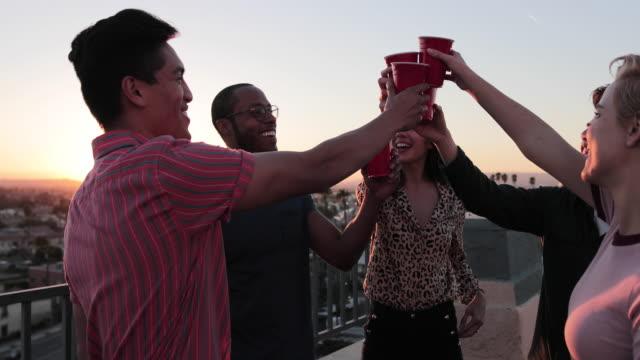 vídeos de stock, filmes e b-roll de group of friends gathering on a rooftop for a celebration - brinde