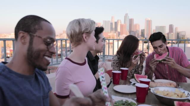 group of friends gathering on a rooftop for a meal - engångsmugg bildbanksvideor och videomaterial från bakom kulisserna