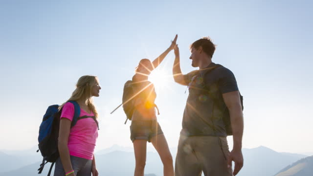 Group of friends giving high five at mountain summit