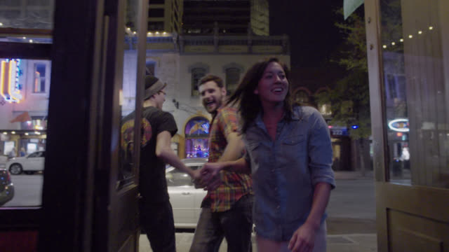 vidéos et rushes de group of friends greet doorman and enter austin bar during south by southwest music festival - bar