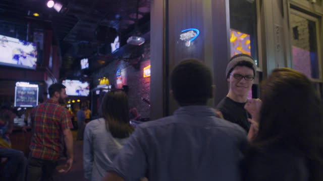 vidéos et rushes de group of friends greet doorman and walk into bar in downtown austin, texas at night - bar