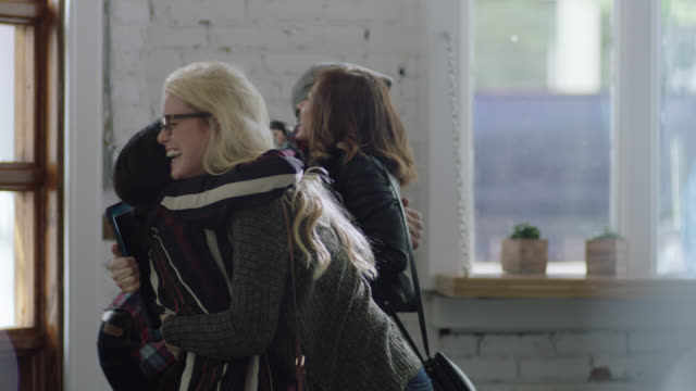 MS SLO MO. Group of friends greet each other with hugs in local coffee shop.