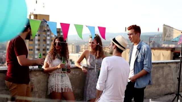 vídeos de stock e filmes b-roll de group of friends hanging out on rooftop of the building - comemoração conceito