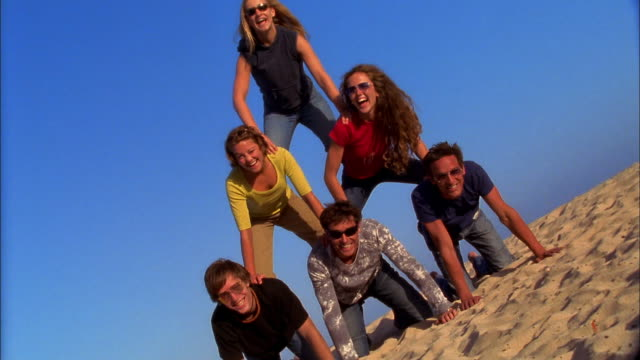 a group of friends happily balance in a human pyramid on the sand. - human pyramid stock videos and b-roll footage