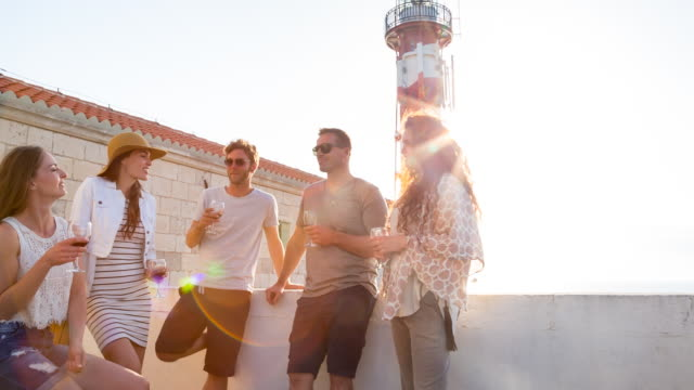 MS group of friends having a drink at lighthouse overlooking mediterranean sea at sunset