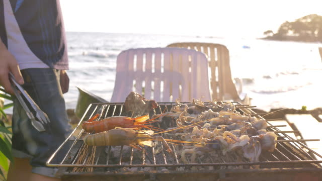 group of friends having barbecue pork shrimp and seafood party event on beach - frutti di mare video stock e b–roll