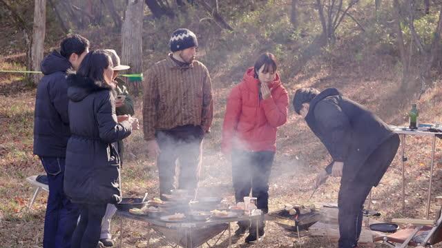 冬の早朝にキャンプ場で朝食を食べる友人のグループ - ピクニック点の映像素材/bロール