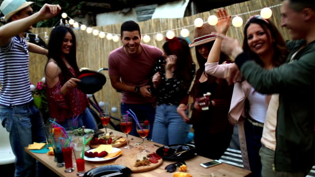 Group of friends having dinner party in backyard