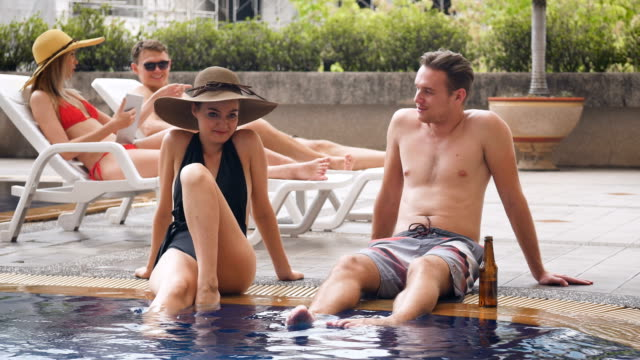 group of friends having enjoy talking with drinking beer and cocktail at swimming pool outdoors, people, vacation and summer concept - poolside stock videos & royalty-free footage