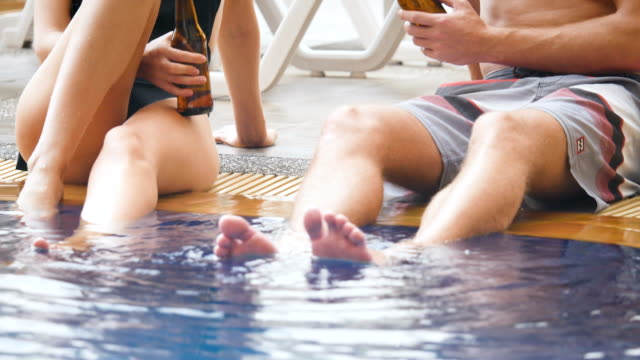 group of friends having enjoy talking with drinking beer and cocktail at swimming pool outdoors, people, vacation and summer concept - poolside stock videos and b-roll footage