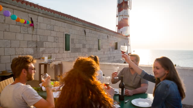 MS group of friends having fish dinner at lighthouse overlooking mediterranean sea at sunset