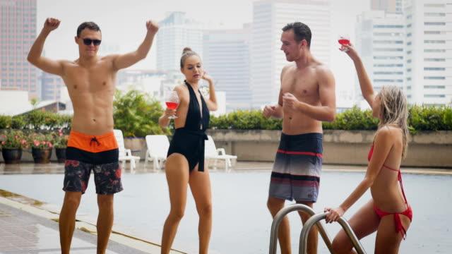 stockvideo's en b-roll-footage met groep vrienden plezier dansen en drinken bier bij het zwembad in openlucht, mensen, vakantie en zomer concept - poolparty