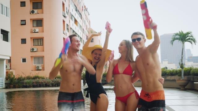 ダンスやスイミング プールの屋外、人々、休暇、夏のコンセプトでビールを飲んで楽しいお友達のグループ - 水鉄砲点の映像素材/bロール
