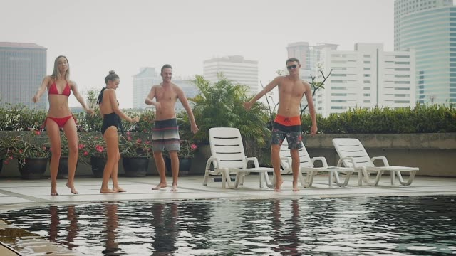 group of friends having fun dancing and drinking beer at swimming pool outdoors, people, vacation and summer concept - swimwear stock videos & royalty-free footage