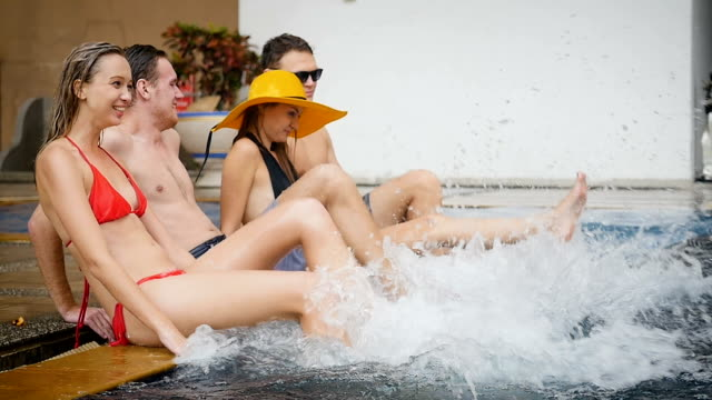 Group of friends having fun playing at swimming pool outdoors, people, vacation and summer concept