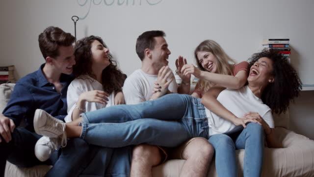 kompis gäng som har kul tillsammans på soffan - bära bildbanksvideor och videomaterial från bakom kulisserna