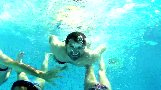 Group of friends having fun underwater.