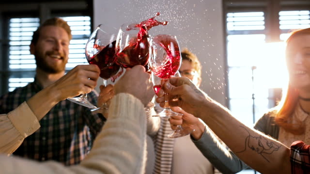 Group of friends having fun while toasting with wine and splashing it.