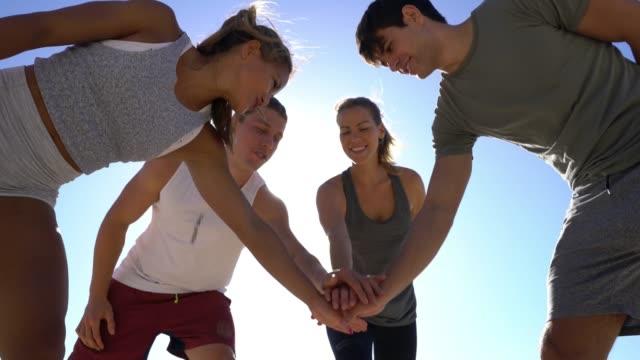 gruppe von freunden, die vor allem mit händen am strand - bodybuilding stock-videos und b-roll-filmmaterial